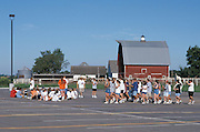Teenagers practicing in groups in school parking lot.