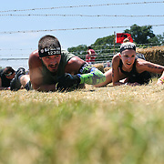 Jack Ziems, (left) and Anne Laffin in action at the barbed wire crawl obstacle during the Reebok Spartan Race. Mohegan Sun, Uncasville, Connecticut, USA. 28th June 2014. Photo Tim Clayton