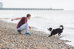 © Licensed to London News Pictures. 29/10/2017. Brighton, UK. A young man plays with his dog on the beach in Brighton as milder weather is hitting the South Coast. Photo credit: Hugo Michiels/LNP
