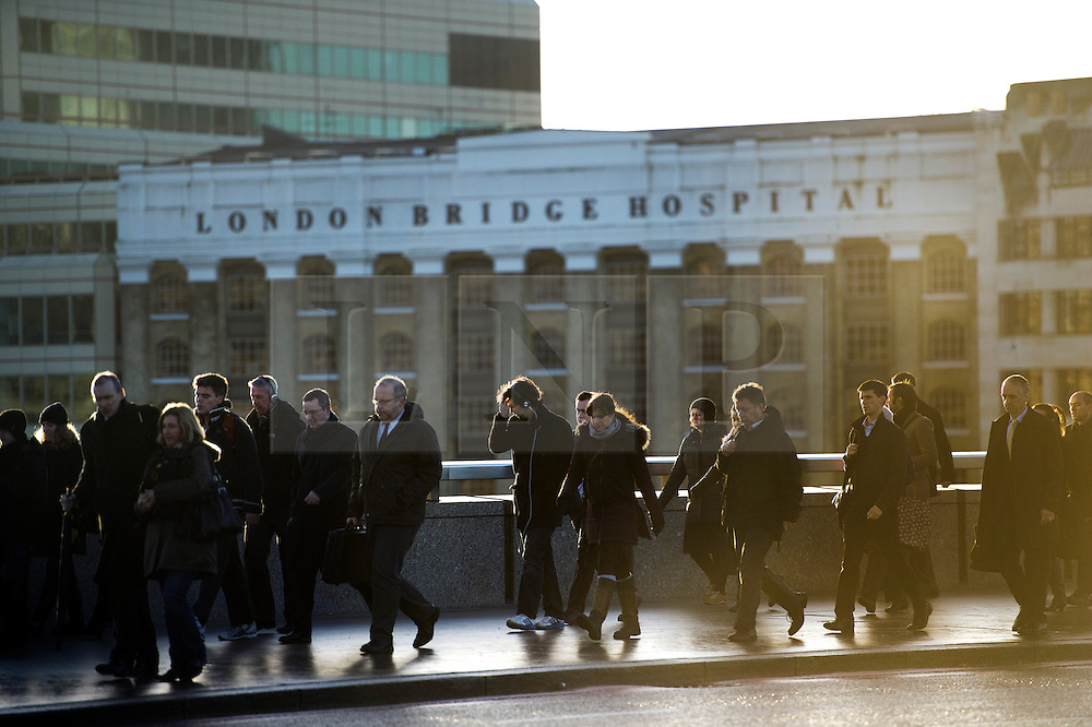 © London News Pictures. 02/01/2014. London, UK.  Commuters make their way across London Bridge early morning in central London as people return to work following the Christmas and New Year break. Photo credit : Ben Cawthra/LNP