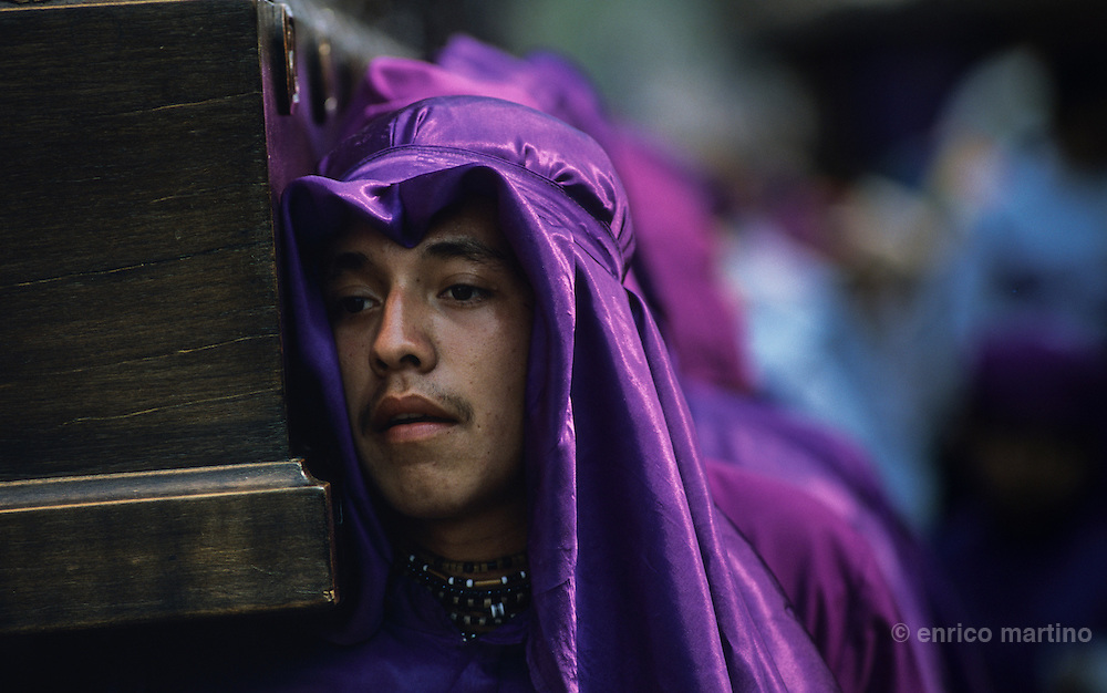 Holy Week. Holy  Thursday, San Francisco procession. The most spectacular Holy Week throughout Latin America, a sort of time machine to find an ancient Spain, where roman soldiers with the faces of Maya peasants interpret for days a choral rite alive in the collective memory as a matter of chronicle. In theatrical scenery of Antigua, between colonial palaces and Baroque churches uncovered by frequent earthquakes and eruptions of nearby volcanoes, processions come one after the other in an increasingly spasmodic crescendo until Holy Friday. From dawn to sunset for thousands of penitents, curucuchos rigorously dressed in purple, is a privilege, often passed down from father to son, to load on the shoulders heavy groups of statues with Jesus Christ, God, the Holy Spirit and the Virgin Mary.