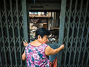 12 NOVEMBER 2015 - BANGKOK, THAILAND:  A woman stands in the doorway of an demolished home at Wat Kalayanmit. Fifty-four homes around Wat Kalayanamit, a historic Buddhist temple on the Chao Phraya River in the Thonburi section of Bangkok, are being razed and the residents evicted to make way for new development at the temple. The abbot of the temple said he was evicting the residents, who have lived on the temple grounds for generations, because their homes are unsafe and because he wants to improve the temple grounds. The evictions are a part of a Bangkok trend, especially along the Chao Phraya River and BTS light rail lines. Low income people are being evicted from their long time homes to make way for urban renewal.       PHOTO BY JACK KURTZ