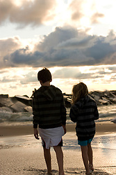 Young boy and girl walking near the surf and rocks at the beach