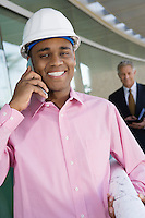 Construction worker using cell phone with businessman behind, portrait
