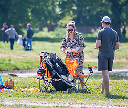 © Licensed to London News Pictures. 26/04/2020. London, UK. A couple set up camp chairs and enjoy food and drink on Wimbledon Common. Members of the public go out to enjoy the warm weather on Wimbledon Common during lockdown where temperatures are expected to reach 21c. London has seen an increase in traffic and busier High Streets as more shops and cafes start to open up during the coronavirus pandemic crisis. Photo credit: Alex Lentati/LNP