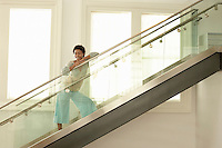 Young woman standing on modern glass stairs portrait