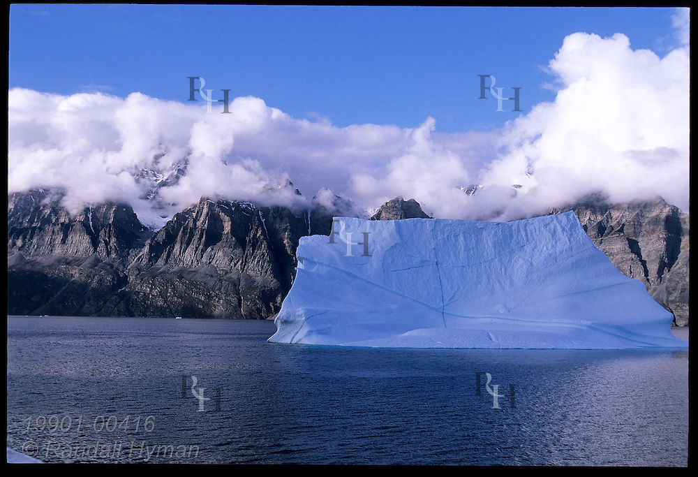 Iceberg drifts northward from Disko Bay along Davis Strait off the mountainous coast of western Greenland.