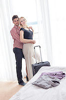 Portrait of young man embracing woman from behind in hotel room