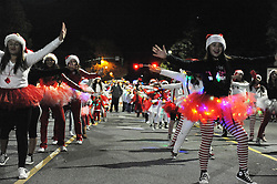 A dance team in Santa hats performs for Salinas residents who turned out for the 14th annual Holiday Parade of Lights.