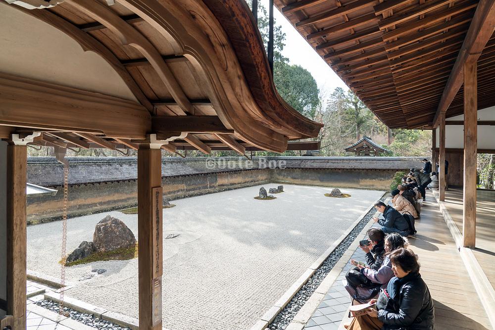 Ryoanji Temple zen garden in Kyoto with sunshine while it rains