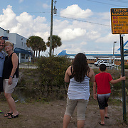 A sign cautions sightseers of alligators in a canal as they gather to see and take pictures of Air Force One, the President's airplane at Palm Beach International Airport, PBI. The Boeing 747 brought President Trump to his winter White House in Palm Beach.<br /> Photography by Jose More