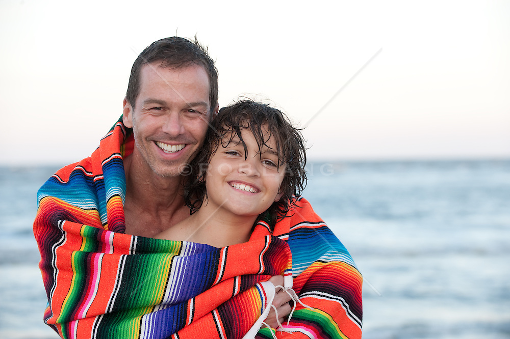 man and boy wrapped in a blanket at the beach in South Carolina