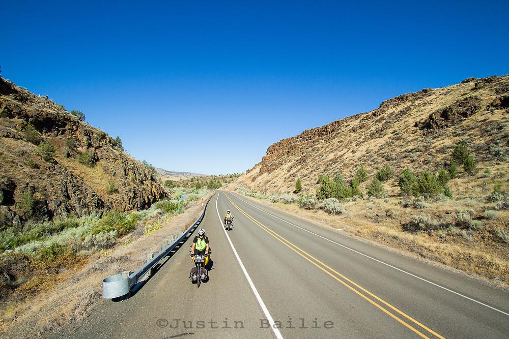 Older couple biking accross the United states. Eastern Oregon; Highway 26.