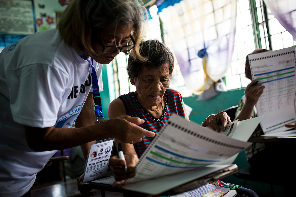 MANILA, PHILIPPINES - MAY 9: Pollwatcher help assists residents to casts their votes in the presidential election at a polling station in Margarita Roxas de Ayala Elementary School, Manila, Philippines on Monday morning of May 9, 2016. <br /> <br /> Photo by Richard A. de Guzman