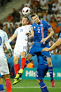 England Forward Jamie Vardy and Iceland defender Birkir Már Sævarsson (2) jump for a header during the Round of 16 Euro 2016 match between England and Iceland at Stade de Nice, Nice, France on 27 June 2016. Photo by Andy Walter.
