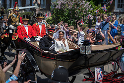 © Licensed to London News Pictures. 19/05/2018. WINDSOR, UK. Prince Harry and Meghan Markle, now The Duke and Duchess of Sussex, ride by in a horse-drawn carriage on a tour of the town after being married in Windsor Castle.  100,000 people were expected to visit the town for what has been billed as the wedding of the year. Photo credit: Stephen Chung/LNP