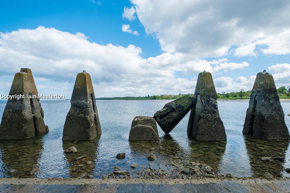 Tidal causeway towards Cramond Island in Edinburgh, Scotland, UK. Concrete structures are wartime anti-submarine defences.
