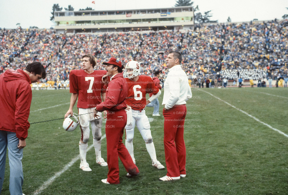 PALO ALTO, CA - NOVEMBER 21:  Quarterback John Elway #7, Mark Cottrell #6, Head Coach Paul Wiggin (white shirt) of Stanford University meet on the sidelines during of the Big Game against the University of California Golden Bears on November 21, 1981 at Stanford Stadium in Palo Alto, California.