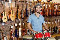 Portrait of a happy man playing bongo drums in music store