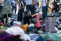 London, June 15th 2017. Mountains of food and clothing donated to the many people who have lost everything and been made homeless in the Grenfell Tower fire of June 14th, by generous Londoners are categorised and stored on a basketball court at the Westway Sports Centre and other locations near to the scene of the fire. PICTURED: A woman sorts through clothes at the West Way Sports Centre.