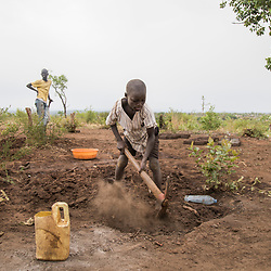 Kenia, 8, a refugee child from South Sudan, digs dirt to build bricks at the Bidi Bidi refugee settlement in north Uganda. These bricks will be used to build huts at the camp.<br />