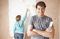 Couple painting interior wall using brush and roller