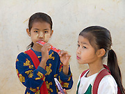 2 Burmese school girls; one with yellow paste on face for sunscreen; Tachilek; Myanmar