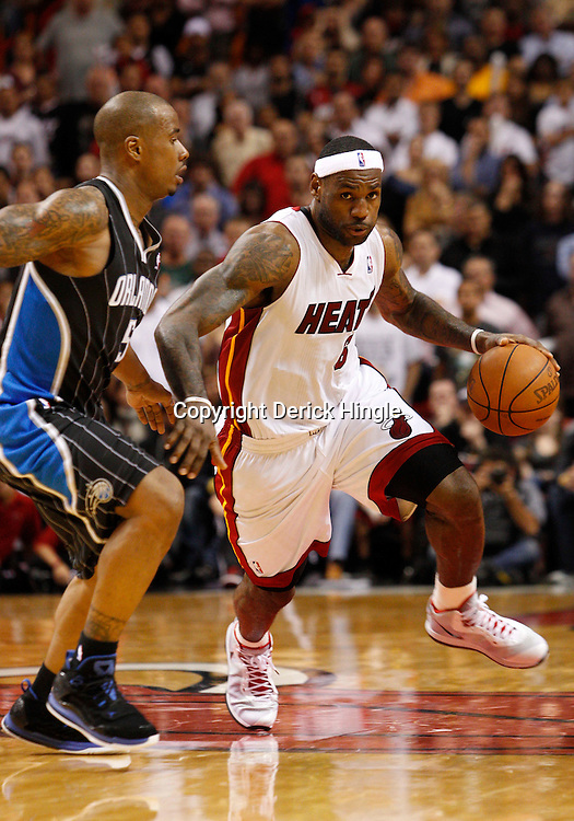 March 3, 2011; Miami, FL, USA; Miami Heat small forward LeBron James (6) drives past Orlando Magic shooting guard Quentin Richardson (5) during the fourth quarter at the American Airlines Arena. The Magic defeated the Heat 99-96.    Mandatory Credit: Derick E. Hingle
