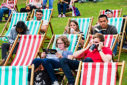 Edinburgh, Scotland, UK. 2 August, 2018. Fine, warm, mainly dry weather in the afternoon  in Edinburgh brings people out into Princes Street Gardens to relax on the deckchairs