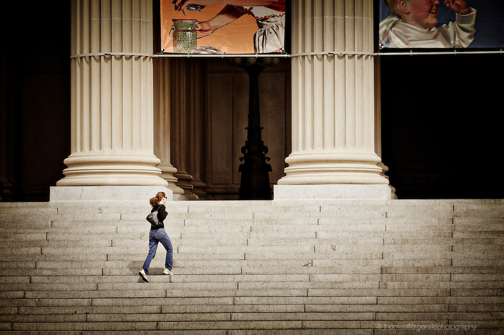 A Woman hurridly climbs the steps to the enterance of the National Archives Building in Washington DC