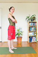 Portrait of a late 20's woman standing in her apartment on a yoga mat...Model Release: 20070608_MR_A