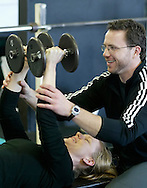 Trainer Chad Tyrell helps Lisa Burke of Highland with her workout at Ignite Fitness in New Paltz on Jan. 30, 2006.