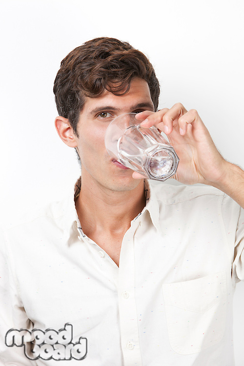 Portrait of young man drinking water against white background