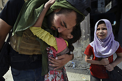 July 2, 2017 - Mosul, Iraq - Mohammed Dylan, a volunteer with Wasel Tasel assisting team from Global Response Management gets a hug from child.  Civilians, many injured and weak, flee continued battle with ISIS in West Mosul amid ruins of the city. (Credit Image: © Carol Guzy via ZUMA Wire)