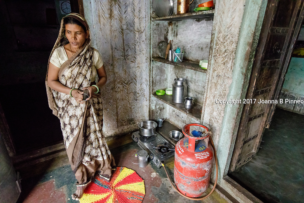 "Shanti Bai next to her LPG cookstove. Shanti Bai makes tea for visitors and her employees using her Greenway Smart Stove to make the tea.  Greenway stoves are made in India. Greenway says that their stoves deliver 60% fuel savings and 70% smoke reduction than the traditional ""chulha"" or mud stove. Shanti Bai runs a weaving business out of her home with seven looms and twenty-eight women employees. She is part of the Jaipur Rug Foundation weavers. Shanti also uses LPG to cook larger meals and the ""chuhla"" to cook the chapati or flatbread that is a staple in Indian homes. Often families who have switched to cleaner cooking stoves still practice ""stove stacking"" which is using more than one type stove at a time, usually the traditional stove and the cleaner one. Some use the traditional stove for specific types of traditional food and some use both at the same time. It can take time for the family cook, usually the woman, to switch completely to the cleaner cooking stove. Shanti Bai says she uses the LPG stove and the Greenway most of the time but still uses the ""chulha"" for making roti or chapatis."