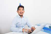 Portrait of happy businessman wearing party hat while working in office