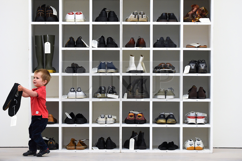 "© Licensed to London News Pictures. 27/09/2018. LONDON, UK. Emlyn Simmonds, aged two and a half, from Lewisham, plays with a pair of size 13 shoes, in front an installation called ""Walk A Mile In My Shoes"", 2006, by Bedwyr Williams  Preview of ""Black Mirror"", a major new exhibition featuring the work of 26 contemporary artists, at the Saatchi Gallery.  The show explores art's role in social satire and how political uncertainty has influenced art of recent years and runs 28 September to 13 January 2019.   Photo credit: Stephen Chung/LNP"