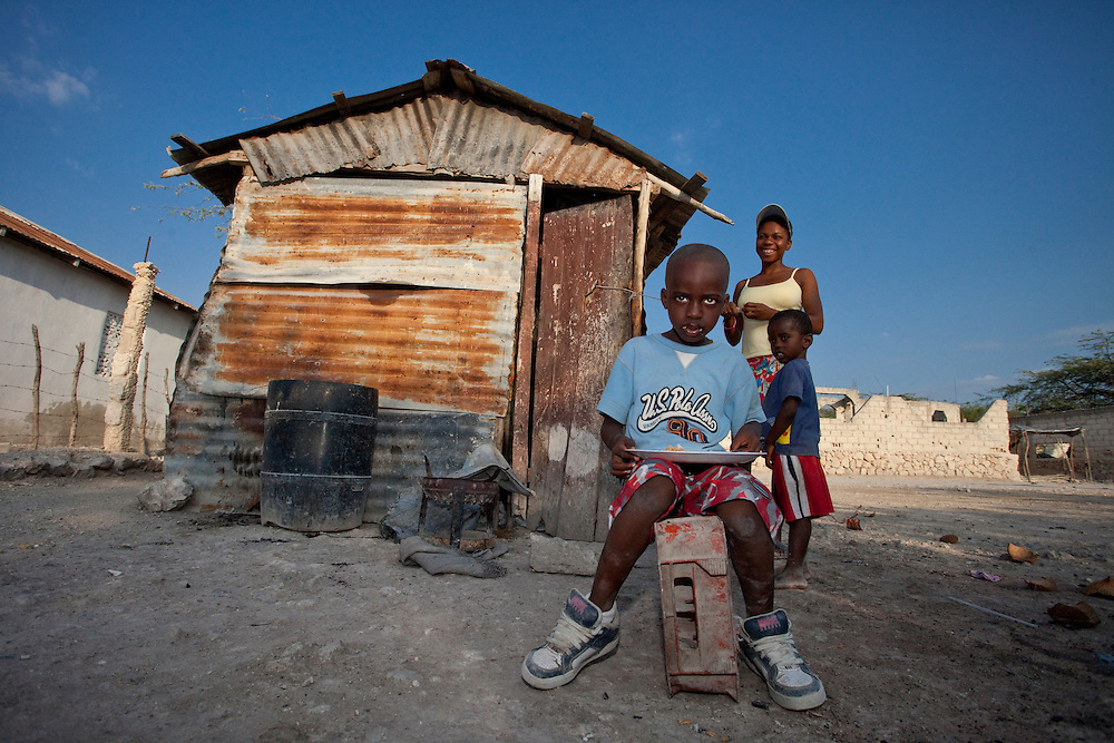 A family gathers outside their home - a small hut made of corrugated iron - in Anse a Galet, le de la Gonave, Haiti