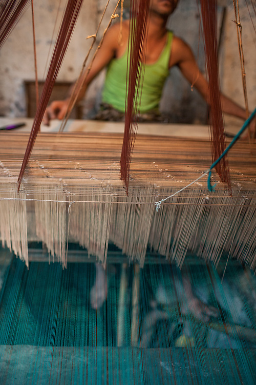 A worker operates the loom that weaves traditional Jamdani sari in Mirpur Benarashi Palli, Dhaka, Bangladesh, a poor Bengali neighborhood.