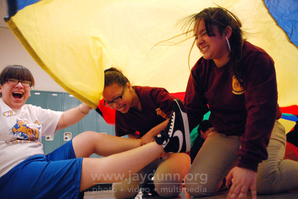 "USA, Chicago, IL, January 19, 2010. Melina Melendez, Lilliana Roman and Atalia Rivera have a good laugh while playing ""Sharks and Lifeguards."" In its tenth year, the mission of Play for Peace is ""bring together children, youth and organizations from communities in conflict"" together. The group believes that in cooperative play, laughter is the best medicine, and has proven itself worthy in places as diverse as Guatemala, Northern Ireland, and the Middle East. In practice at Roberto Clemente High School in Chicago's rough-and-tumble Humboldt Park area, students having a Play for Peace ""meeting"" made remembering people's names' working as a team, encouragement, and partnership a priority in over an hour of flat-out fun. These upbeat, multi-racial students will go on to use their open minds in mentoring younger kids in the spirit of friendship and equality.  Photo for Hoy by Jay Dunn."