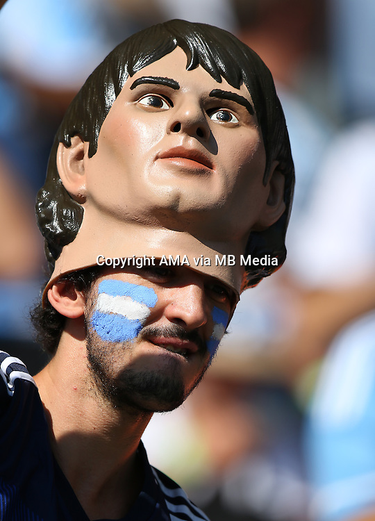 A Fan of Argentina wears a Lionel Messi mask on his head