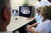 Nederland, Nijmegen, 27-10-2005..Artsen,medici, in een ziekenhuis kijken naar een beeldscherm waarop collega's te zien zijn die op een andere lokatie zijn. Via een directe videoverbinding kunnen zij informatie uitwisselen en overleg plegen. Video conference.