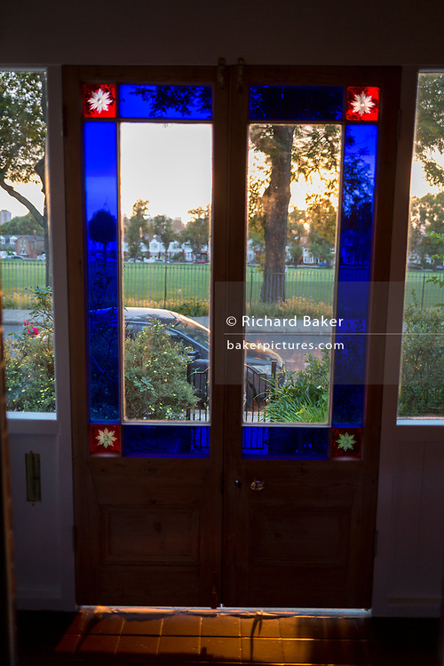Original stained glass from newly restored vintage 100 year-old French Doors, in evening sunight in a residential porch, on 12th June 2018, in London, England.