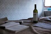 L'aquila, Abruzzo, Italia. 27.03.2014. Siste tegn til liv. En flaske rød vin og en bok ligger igjen på bordet i et hjem i sentrum av den jordskjelvrammede byen. L'aquila, 6. april 2009 kl. 03:32: Et jordskjelv som måler 6.3 ryster byen. 309 mennesker mister livet. Fem år senere sliter de som overlevde fortsatt med etterskjelvene, i form av en guffen cocktail av uærlige offentlige tjenestemenn, mafia og 494 millioner øremerkede euro på avveie. Fotografier til bruk i feature i DN lørdag 05.04.2014. Foto: Christopher Olssøn.