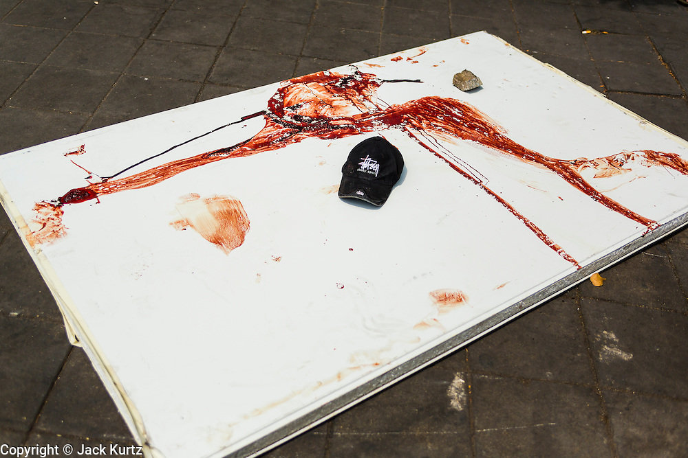 18 FEBRUARY 2014 - BANGKOK, THAILAND:  Blood on a board that was used as a stretcher to rush a wounded person to medical help after police clashed with protestors in Bangkok. Anti-government protestors aligned with Suthep Thaugsuban and the People's Democratic Reform Committee (PDRC) clashed with police Tuesday. Protestors opened fire on police with at rifles and handguns. Police returned fire with live ammunition and rubber bullets. The Bangkok Metropolitan Administration's Erawan Emergency Medical Centre reported that three civilians and a policeman were killed and 64 others were injured in the clashes between police and protesters.   PHOTO BY JACK KURTZ