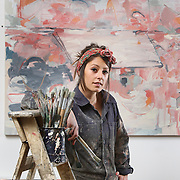 A graduate artist poses in her studio