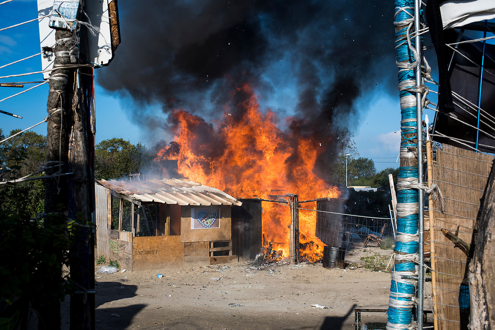 A structure goes up in flames, the first of what would be many fires over several days,  at The Jungle refugee camp where authorities were processing refugees for relocation on October 25, 2016 in Calais, France.