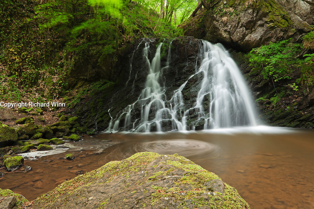 The lower falls at Fairy Glen on the Black Isle of Scotland, with a moss-covered rock in the foreground.