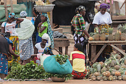 Women and teenage girl at a roadside market in Bouake, Cote d'Ivoire on Sunday July 14, 2013.