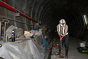 A worker demonstrates how the track bed can be raised in construction of subway lines.